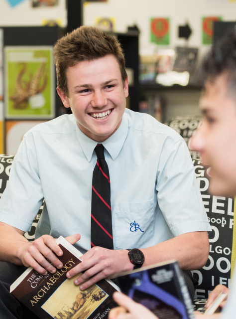 A student smiles while looking at a classmate