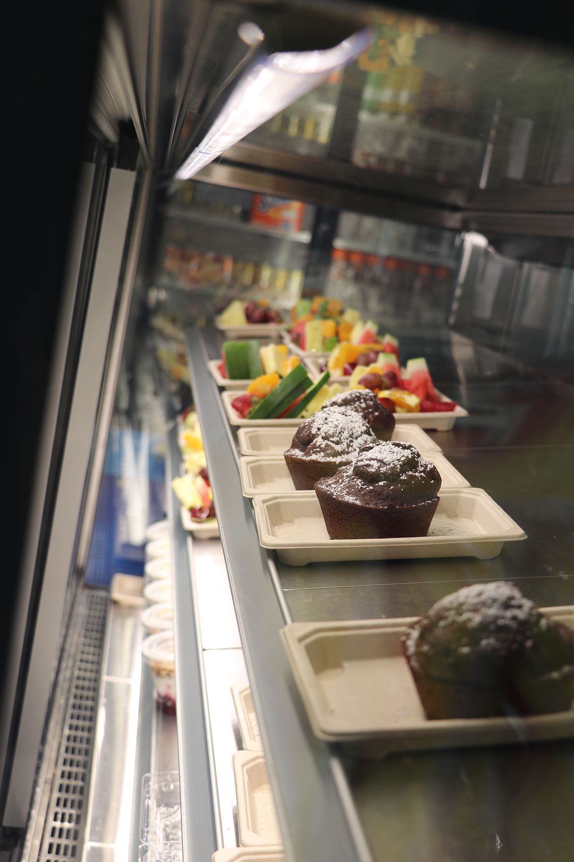 The display fridge in the canteen, with fruit and chocolate muffins